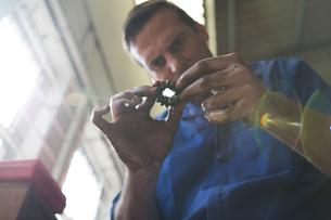 Male car mechanic looking at car part in repair garageの写真素材 [FYI03600024]