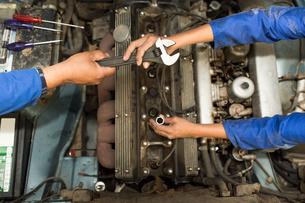 Overhead view of car mechanics hands and car engine in repair garageの写真素材 [FYI03600026]