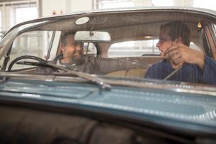 Two car mechanics talking in front seat of vintage car in repair garageの写真素材 [FYI03600028]