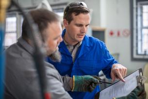 Male car mechanics pointing at clip board in repair garageの写真素材 [FYI03600029]