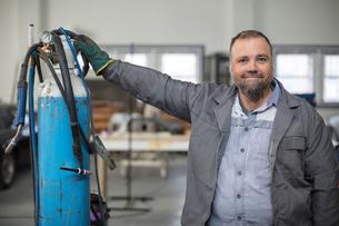 Portrait of mature male car mechanic in repair garageの写真素材 [FYI03600031]