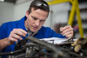 Male car mechanic with clip board checking car engine in repair garageの写真素材 [FYI03600032]