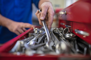 Hands of male car mechanic selecting wrench from tool box  in repair garageの写真素材 [FYI03600036]