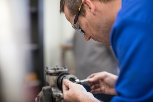 Male car mechanic working in repair garageの写真素材 [FYI03600037]