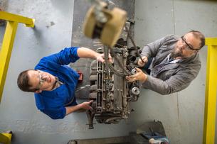 Overhead view of  car mechanics hoisting car engine in repair garageの写真素材 [FYI03600038]
