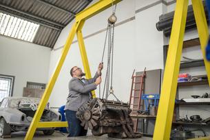 Male car mechanic hoisting car engine in repair garageの写真素材 [FYI03600039]