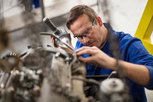 Car mechanic inspecting car part in repair garageの写真素材 [FYI03600041]