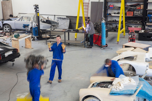 Car mechanic team on the move and busy in repair garageの写真素材 [FYI03600042]