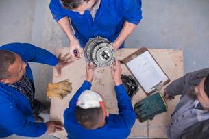 Overhead view of car mechanic team inspecting car part in repair garageの写真素材 [FYI03600043]