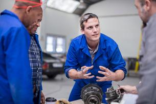 Car mechanic team discussing car part in repair garageの写真素材 [FYI03600044]