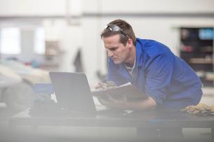 Car mechanic with clipboard looking at laptop in repair garageの写真素材 [FYI03600047]