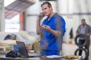 Car mechanic making smartphone call in repair garageの写真素材 [FYI03600048]