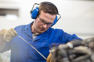 Car mechanic checking oil in repair garageの写真素材 [FYI03600049]