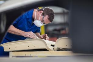 Car mechanic sanding car door in repair garageの写真素材 [FYI03600050]