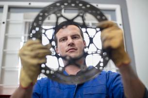 Car mechanic inspecting circular car part in repair garageの写真素材 [FYI03600052]