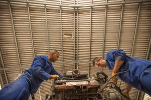 Low angle view of car mechanics inspecting car engine in repair garageの写真素材 [FYI03600053]