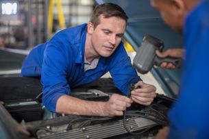 Car mechanics inspecting car engine in repair garageの写真素材 [FYI03600054]