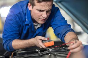 Car mechanic testing car engine in repair garageの写真素材 [FYI03600056]