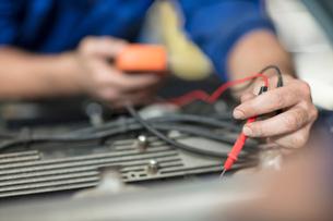 Car mechanic testing car engine in repair garageの写真素材 [FYI03600058]