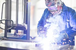 Car mechanic welding in repair garageの写真素材 [FYI03600059]