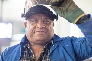 Portrait of mature male car mechanic in welding mask at repair garageの写真素材 [FYI03600061]