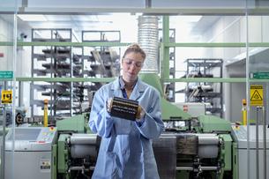 Female operator with bobbin of carbon fibre in carbon fibre production facilityの写真素材 [FYI03600078]