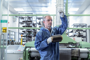 Operator with bobbin of carbon fibre in carbon fibre production facilityの写真素材 [FYI03600079]