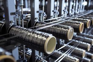 Carbon fibre bobbins on loom in carbon fibre production facilityの写真素材 [FYI03600087]