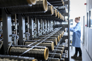 Operator with carbon fibre bobbins on loom in carbon fibre production facilityの写真素材 [FYI03600088]