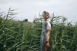 Side view of woman in tall grass looking away, Odessa, Odeska Oblast, Ukraine, Europeの写真素材 [FYI03600126]