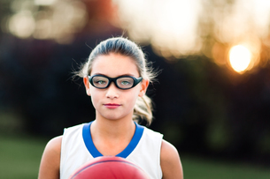 Portrait of girl wearing sports goggles holding basketballの写真素材 [FYI03600169]