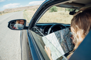 View over shoulder of woman sitting in car looking at mapの写真素材 [FYI03600228]