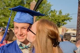 Girl kissing boy on cheek at graduation ceremonyの写真素材 [FYI03600301]