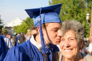 Teenage boy kissing grandmother at graduation ceremonyの写真素材 [FYI03600303]