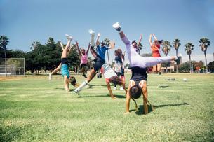 Schoolgirl soccer team doing cartwheel celebration on school sports fieldの写真素材 [FYI03600439]