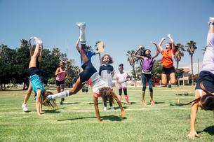 Schoolgirl soccer team doing cartwheel celebration on school sports fieldの写真素材 [FYI03600440]