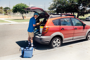Male sport teacher packing car boot at schoolの写真素材 [FYI03600527]