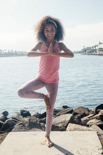 Portrait of schoolgirl practicing yoga tree pose by lakesideの写真素材 [FYI03600547]