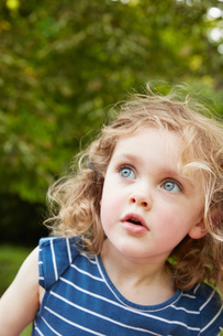 Portrait of blond wavy haired girl with blue eyes gazing in parkの写真素材 [FYI03600669]
