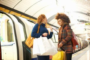 Two young women standing on underground train platform, holding shopping bagsの写真素材 [FYI03600708]
