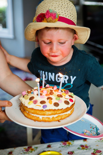 Boy blowing out candles on birthday cakeの写真素材 [FYI03600747]