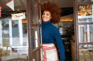Portrait of small business owner in cafe doorway looking at camera smilingの写真素材 [FYI03600798]