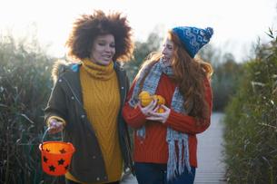 Friends carrying miniature pumpkins and bucketの写真素材 [FYI03600830]