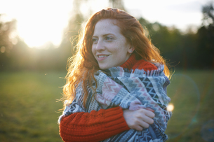 Young woman in rural setting, wrapped in blanketの写真素材 [FYI03600914]