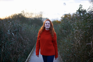 Portrait of young woman walking along rural pathwayの写真素材 [FYI03600924]