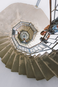 Low angle portrait of three young adult friends looking down from spiral staircase, Como, Lombardy,の写真素材 [FYI03601020]
