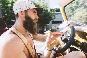 Young male hipster on road trip using smartphone navigation, Como, Lombardy, Italyの写真素材 [FYI03601025]