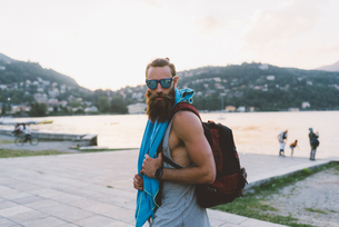 Portrait of young male hipster with backpack at lake Como, Lombardy, Italyの写真素材 [FYI03601035]