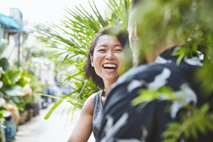 Multi ethnic couple laughing together in residential alleyway, Shanghai French Concession, Shanghai,の写真素材 [FYI03601092]