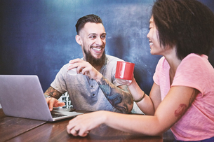 Multi ethnic hipster couple in cafe using laptop, Shanghai French Concession, Shanghai, Chinaの写真素材 [FYI03601100]